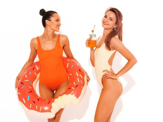 夏のカラフルな水着水着で2人の美しいセクシーな笑顔の女性。分離された女の子。ドーナツリロインフレータブルマットレスと新鮮なカクテルスムージードリンクを飲んで面白いモデル 無料写真