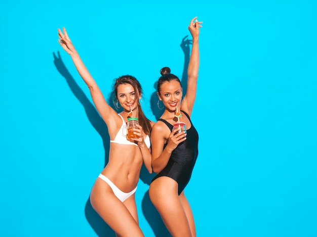夏の白と黒の水着水着で2人の美しいセクシーな笑顔の女性。狂ったトレンディな女の子。青に分離された面白いモデル。新鮮なカクテルスムージードリンクを飲みます。 無料写真