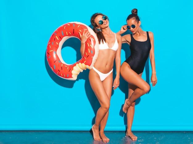 夏の白と黒の水着水着で2人の美しいセクシーな笑顔の女性。サングラスの女の子。ドーナツリロインフレータブルマットレスを楽しんで肯定的なモデル。青い壁に分離 無料写真