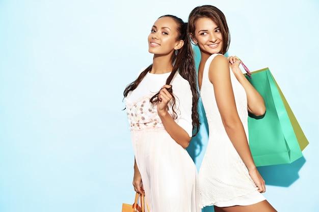 買い物袋を保持している2人の若いセクシーなスタイリッシュな笑顔ブルネット女性の肖像画。夏の流行に敏感な服を着た熱い女性。青い壁を越えてポーズポジティブモデル 無料写真