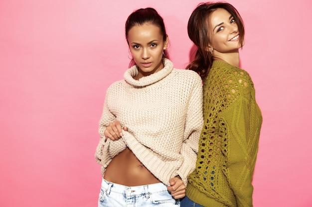 2人の美しい笑顔の豪華な女性。ピンクの壁にスタイリッシュな白と緑のセーターで立っている女性。 無料写真