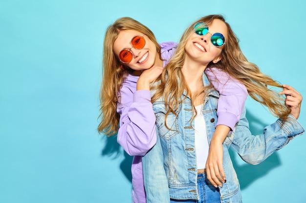 トレンディな夏服で流行に敏感な女性を笑顔2人の若い美しいブロンド。サングラスの青い壁に近いポーズセクシーな屈託のない女性。夢中になってハグするポジティブなモデル 無料写真