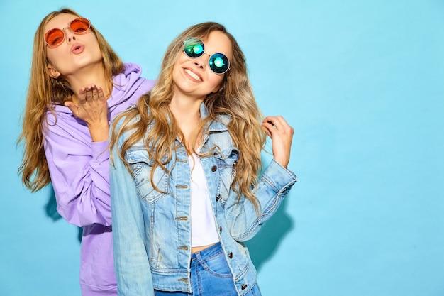 トレンディな夏服で流行に敏感な女性を笑顔2人の若い美しいブロンド。サングラスの青い壁に近いポーズセクシーな屈託のない女性。ポジティブなモデルが夢中になる 無料写真