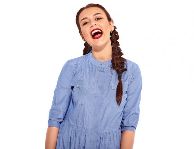 明るいメイクで若い幸せな笑顔の女性モデルと分離された夏のカラフルな青いドレスの手で2つのおさげの赤い唇の肖像画 無料写真