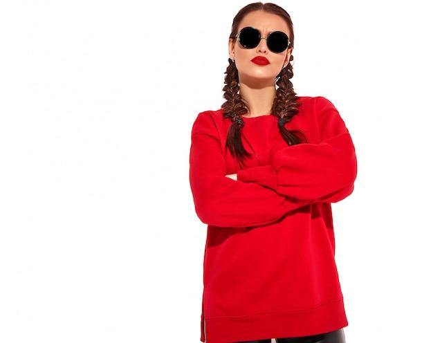 明るいメイクと2つのおさげ髪と分離された夏の赤い服のサングラスとカラフルな唇を持つ若い幸せな笑顔の女性モデルの肖像画。クロスアーム 無料写真
