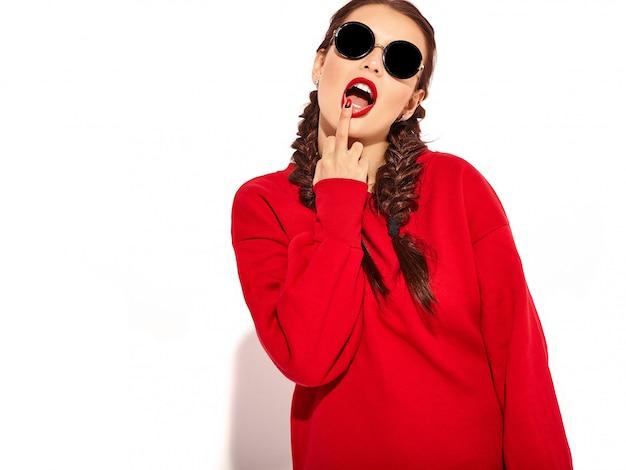 明るいメイクと2つのおさげ髪と分離された夏の赤い服のサングラスとカラフルな唇を持つ若い幸せな笑顔の女性モデルの肖像画。中指をなめる、サインオフファック 無料写真
