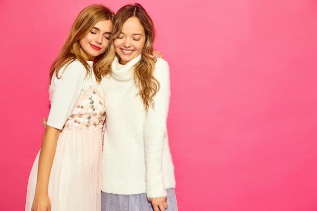 トレンディな夏の白い服の2人の若い美しい笑顔の女性 無料写真