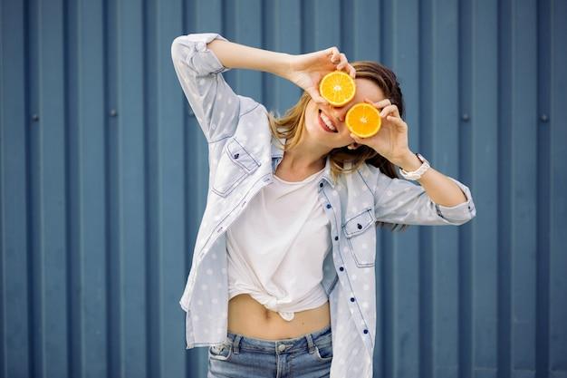 2つのオレンジを手で保持して笑顔の女性 無料写真
