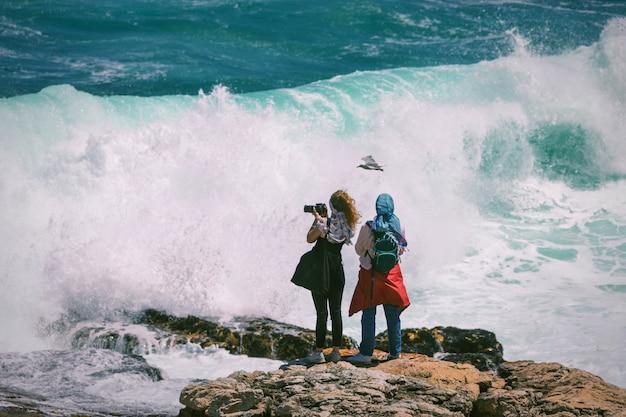 南アフリカのヘルマナスで巨大な危険な波とその上を飛んでいるカモメに直面して写真を撮る2人の若い女性観光客 Premium写真