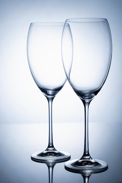 細い脚にワインのない2つのガラスのゴブレットが鏡面に立っています。 Premium写真