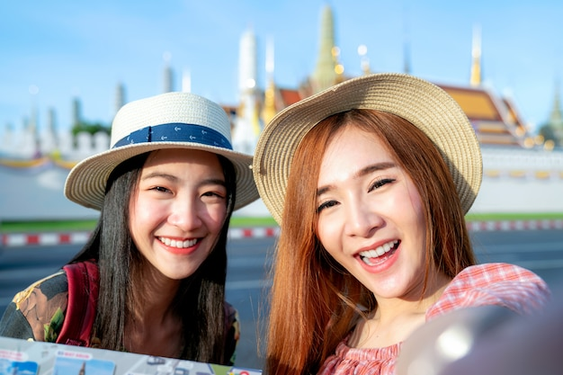 2つのアジアのガールフレンドが旅行し、グランドパレスとワットプラケオで写真を撮る Premium写真