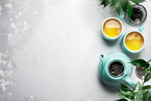 灰色のコンクリートテーブルの上のティーポットと緑茶2杯 Premium写真