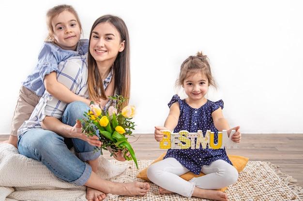 幸せな母の日で2人の妹がお母さんを祝福します。子供たちがハグして母にキスします。 無料写真