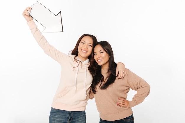 矢印を保持している2つのアジアの正の女性姉妹。 無料写真