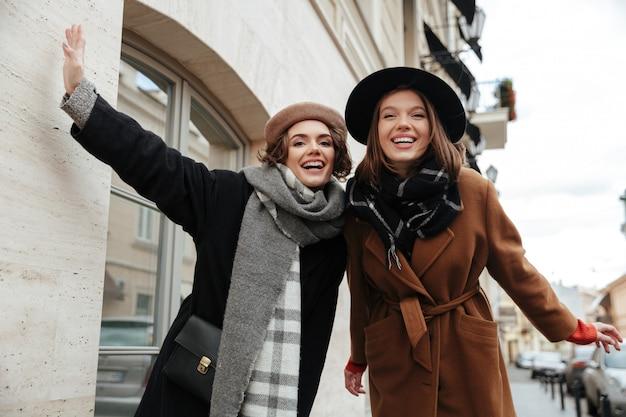 秋の服を着て歩く2人の陽気な女の子の肖像画 無料写真