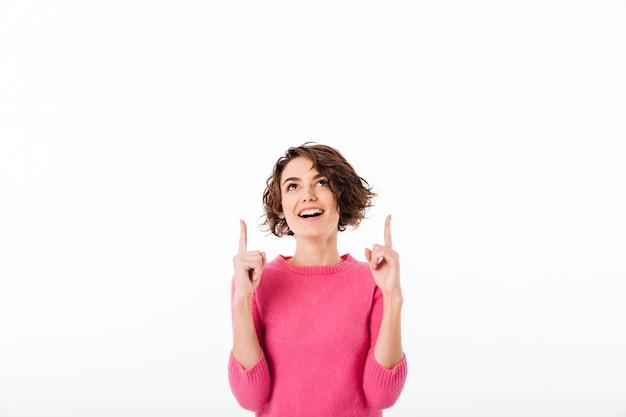 2本の指を指している幸せなかわいい女の子の肖像画 無料写真