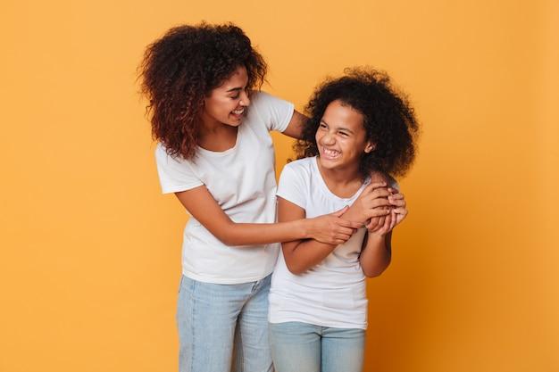立っている間楽しんで2人の幸せなアフロアメリカンの姉妹 無料写真