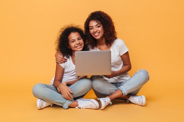 2 усмехаясь афро американских сестры держа портативный компьютер Бесплатные Фотографии