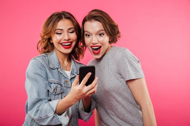 携帯電話を使用して2つの笑顔の女性の友人。 無料写真