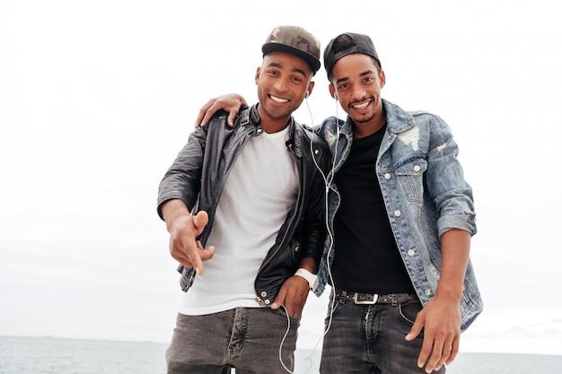 Счастливые 2 молодых африканских друз друзей слушая музыка. Бесплатные Фотографии