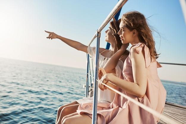 ヨットの船首に座って、海辺を指さしながら何かを見ている2人の魅力的なヨーロッパの女性。 無料写真