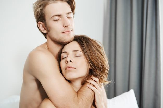 目を閉じてロマンチックな笑顔でベッドで抱き締める愛の2つの美しい柔らかい若い大人のクローズアップショット。新婚旅行のカップルは彼らが一緒に目を覚ました最初の朝を楽しむ 無料写真