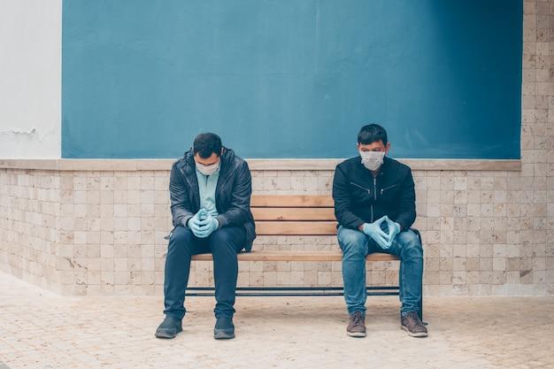日中庭で心配してベンチに座っている2人の男性。 無料写真