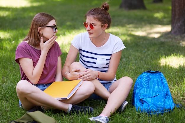2人の女性の仲間は、会話をしながらお互いを見つめ、足を組んで座って、大学でニュースについて話し合い、本を持ち、緑の芝生に座って心地よく感じます。人とライフスタイルのコンセプト Premium写真