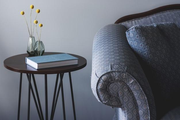 本と小さな植物が付いた小さな丸いテーブルの近くに青いソファのショットと黄色の植物が置かれた2つの花瓶 無料写真