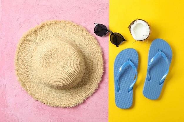 麦わら帽子、フリップフロップ、サングラス、2つのトーンの背景、テキストとトップビューのためのスペースにココナッツ。夏休みのコンセプト Premium写真