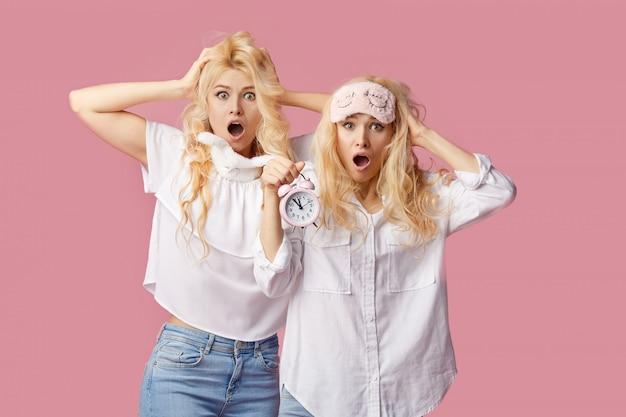 ピンクの壁にパジャマと睡眠マスクの2人の双子の眠れない若い女性。目覚まし時計が女の子を起こしました Premium写真