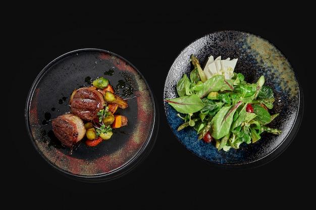 2つの食欲をそそる料理-フェタチーズとトマトのサラダ、黒い表面にスタイリッシュなセラミックプレートのビーフステーキ。上面図。メニューのフード写真 Premium写真
