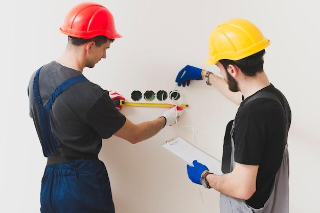 壁に措置を取っている修理士2人 無料写真