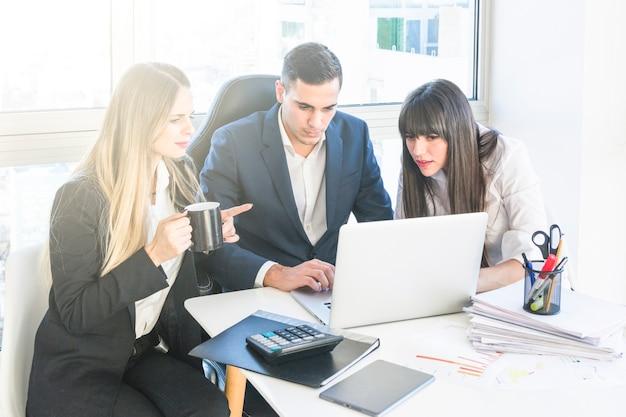オフィスで働く2人の女性と座っているビジネスマン 無料写真