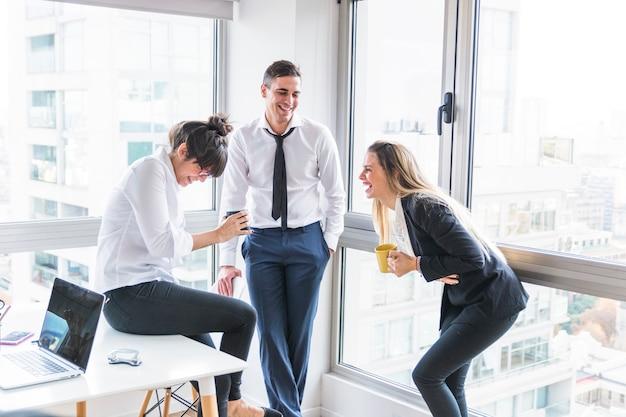 オフィスで笑っている2人のビジネスマンを見ているビジネスマン 無料写真