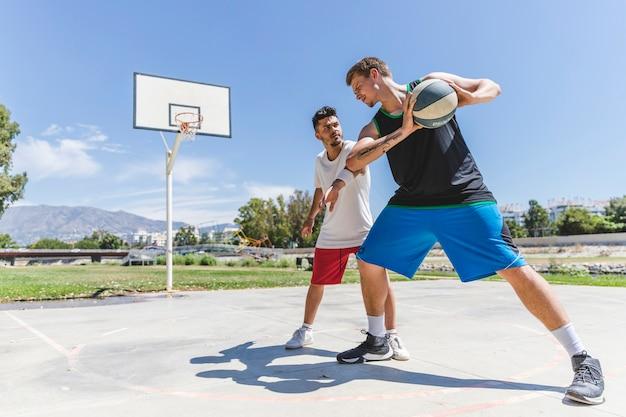 都市の裁判所で早朝に遊ぶ2人の若い男性プレーヤー 無料写真