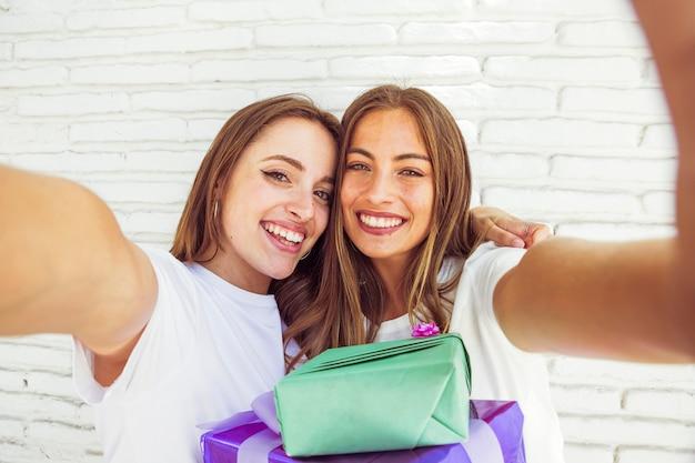 レンガの壁の前に誕生日の贈り物と2つの笑顔の女性の友達 無料写真