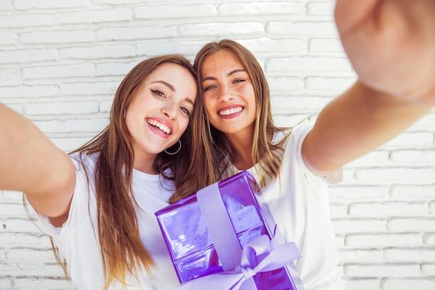 2つの笑顔の女性の友達と誕生日プレゼント 無料写真