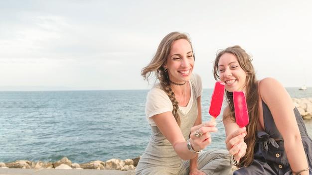 赤いキャンディーを示す海岸に座っている2人の女性の友達を笑って 無料写真