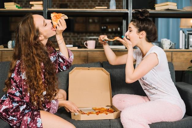 2人の空腹の若い女性がピザを食べる 無料写真