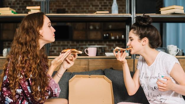 ピザを食べる2人の女性の友人の側面図 無料写真