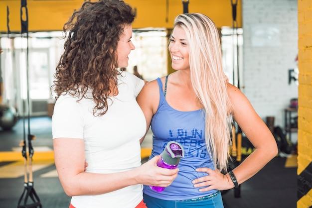 フィットネスクラブでお互いを見ている2人の幸せなフィットの女性 無料写真