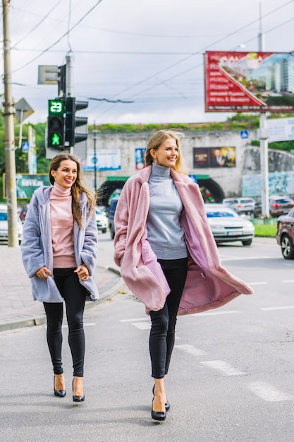 道路を横断する毛皮のジャケットでスタイリッシュな2人の若い女性 無料写真