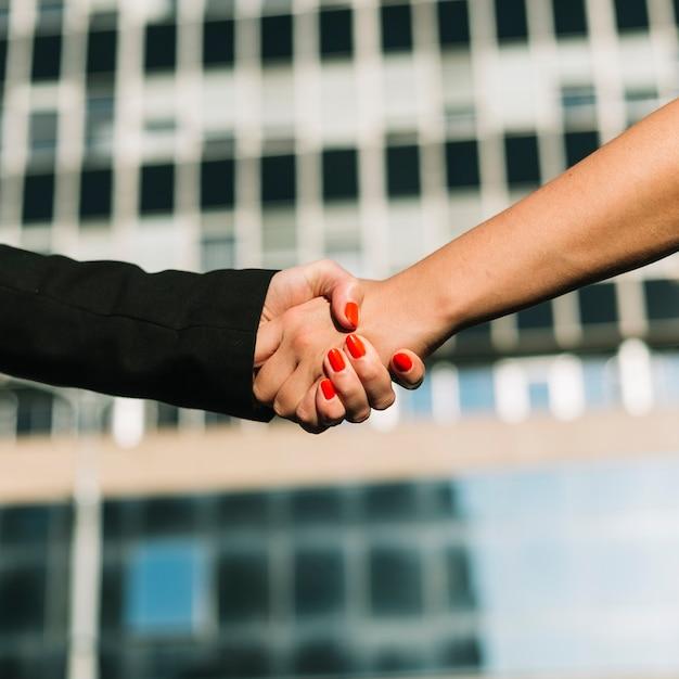 バックグラウンドで青い建物と握手2人のビジネスマン 無料写真