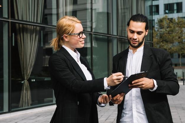 2人のビジネスマンが屋外でクリップボードを介して事業プロジェクトを議論します。 無料写真