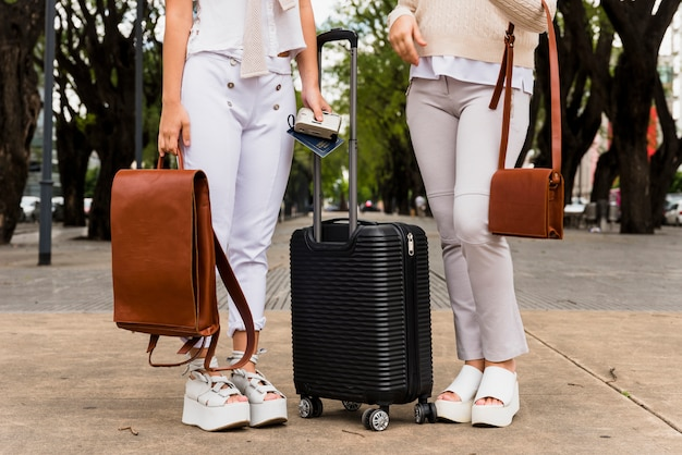 黒のスーツケースとその革のバッグと一緒に立っている2人の若い女性の低いセクション 無料写真