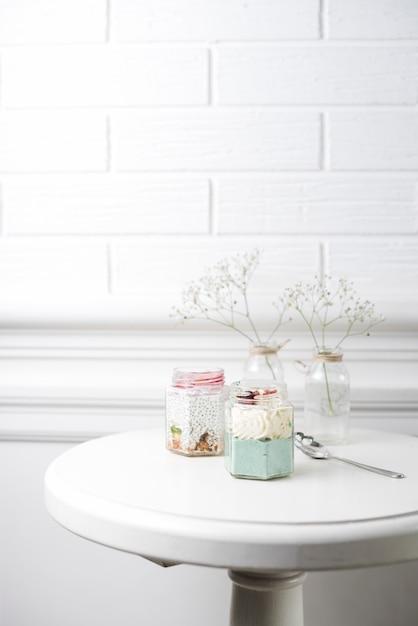 白い壁にテーブルの上のスプーンで2つのスムージーガラス瓶 無料写真