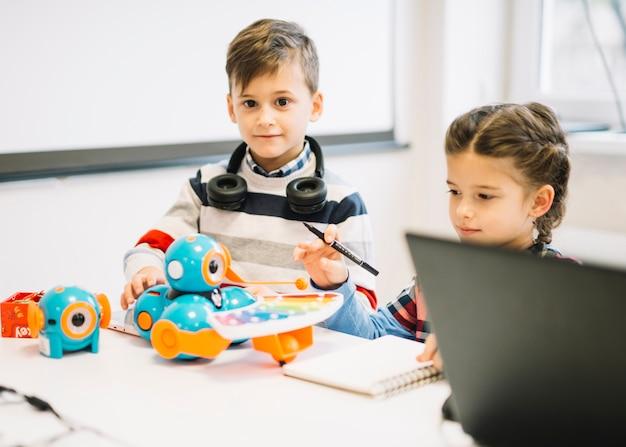 教室でデジタル玩具で遊ぶ2人の子供 無料写真