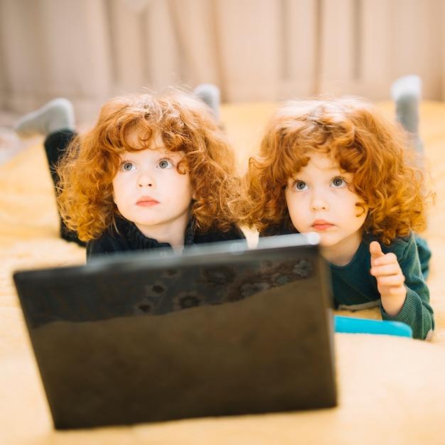 見上げるノートパソコンの前に横になっている2つのかわいい双子のクローズアップ 無料写真