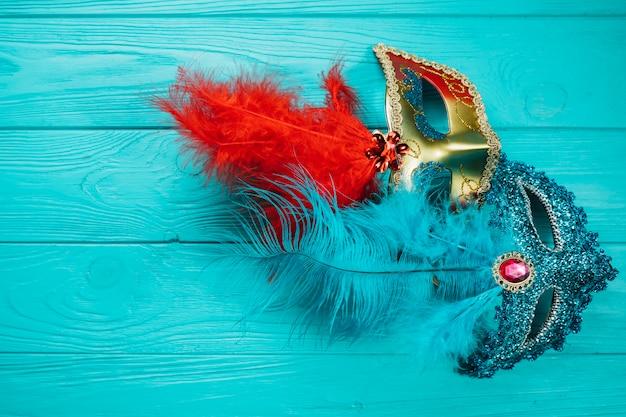 青い木製のテーブルの上の2つの赤と青のベネチアンカーニバルマスク 無料写真